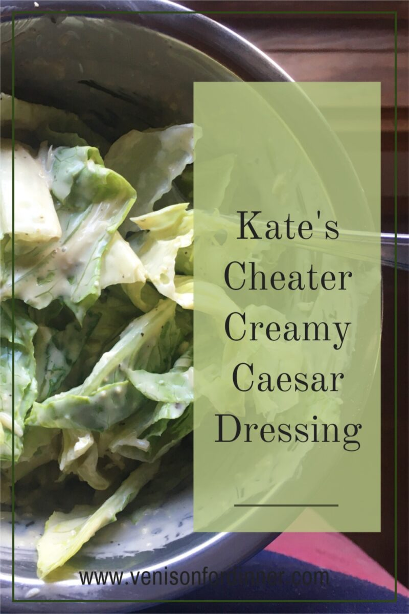 Caesar dressing on lettuce from above in metal bowl