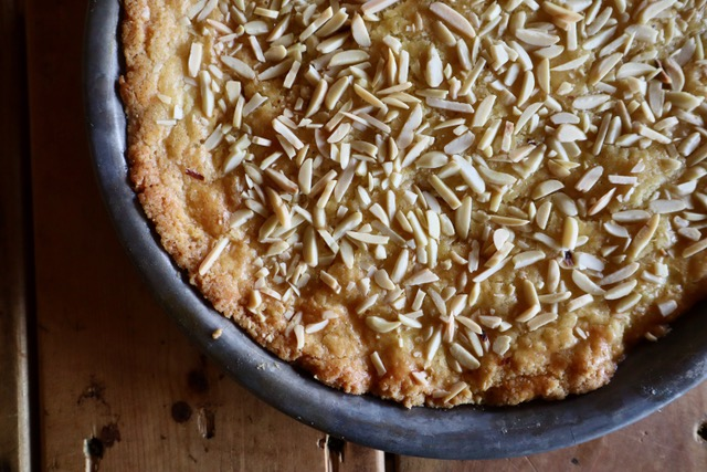 Almond Ring shortbread cake covered with slivered almonds in a round pan.