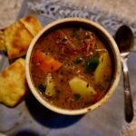 Bowl of stew with parsnips, carrots, and wild game, resting on a blue napkin with a biscuit.