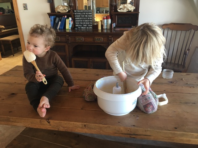 Two girls on a wood table licking the spatulas from mixing cookie dough.