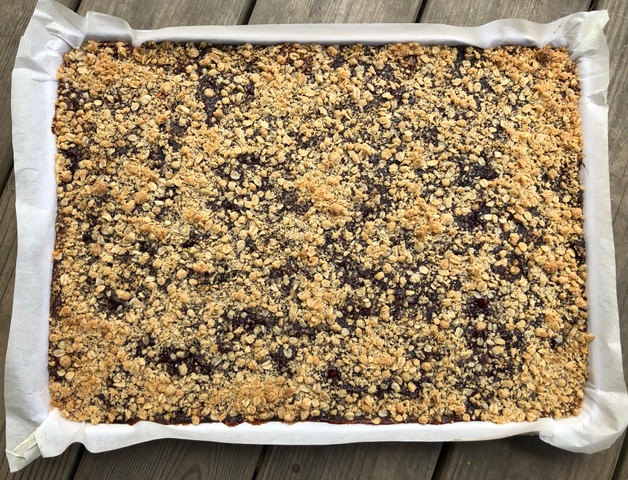 Oatmeal jam bars in a parchment-lined sheet pan.