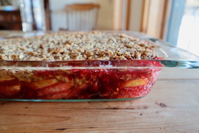 Apple berry crisp in a clear glass baking dish.