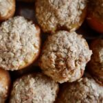 Close up view of oatmeal topping baked into peach halves.