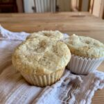 Side view of lemon poppy seed muffins in papers.