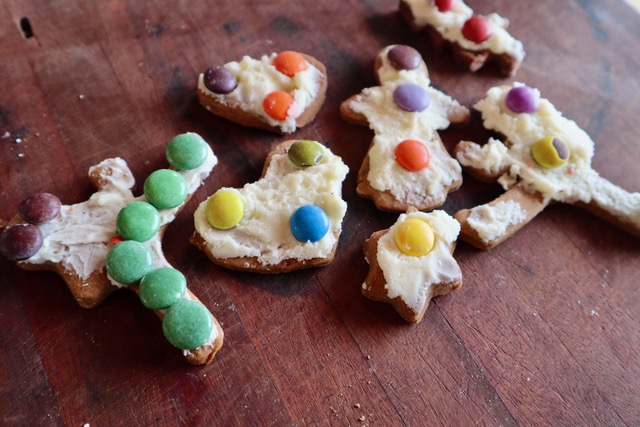 Gingerbread cutout cookies with frosting and chocolate candies.