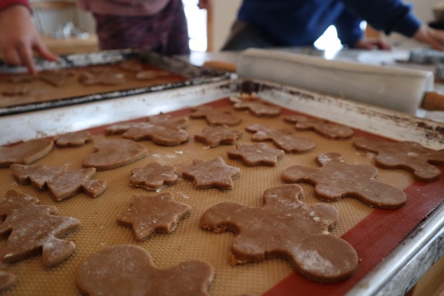 Gingerbread cutouts on a baking sheet ready to go in the oven.