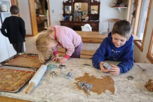 Kids cutting out gingerbread shapes from dough on the counter.