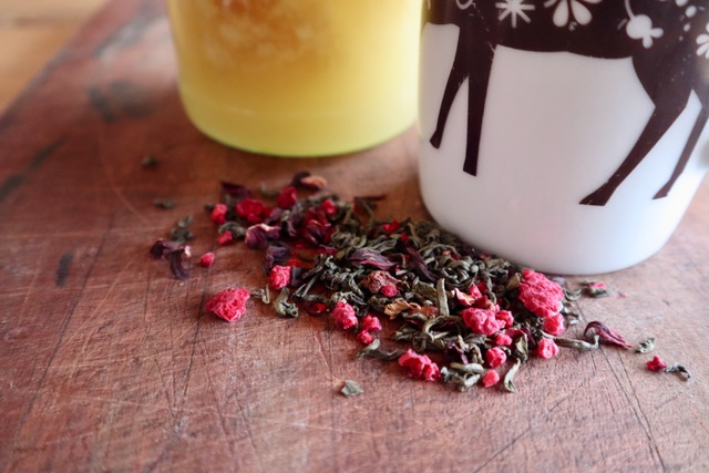 Small pile of dried raspberries, hibiscus, and green tea leaves.