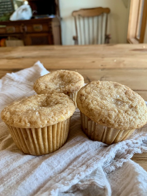 Applesauce muffins cooling on a dish towel.