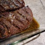 Tilting a glass pan with finished venison steak in it to show the delicious pan juices.