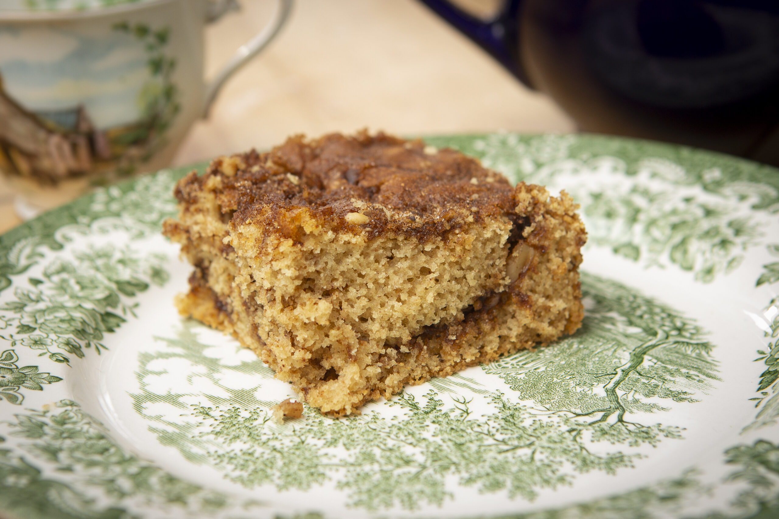 Gluten-free cinnamon crumb coffee cake on a green patterned plate.