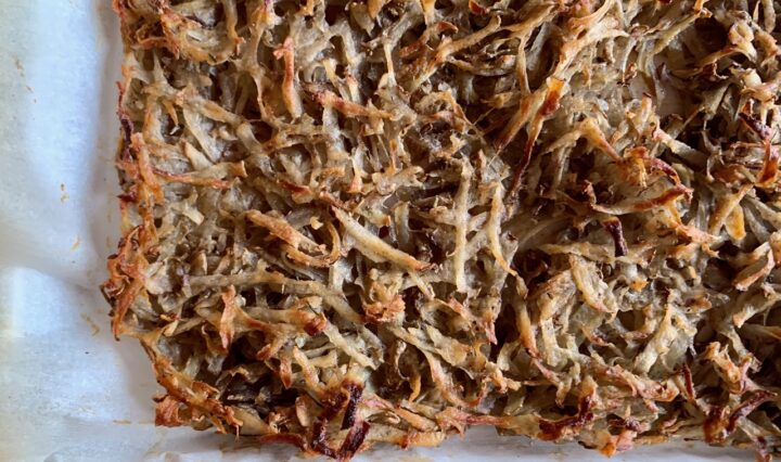 Shredded potatoes pressed into a parchment-lined sheet pan.