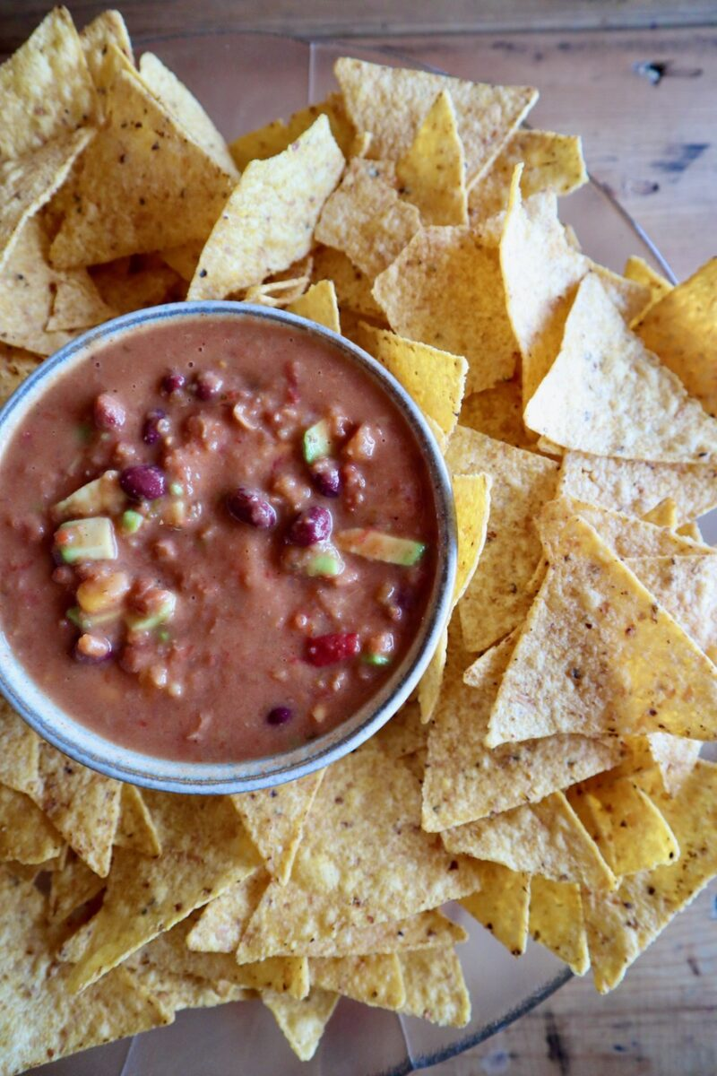 Avocado bean dip recipe in a bowl surrounded by tortilla chips.
