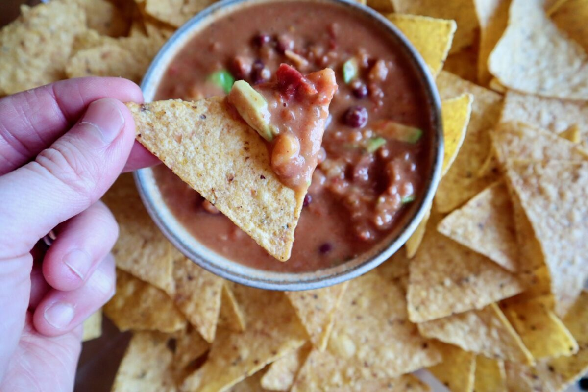 Hand holding a tortilla chip that has scooped up avocado bean dip.