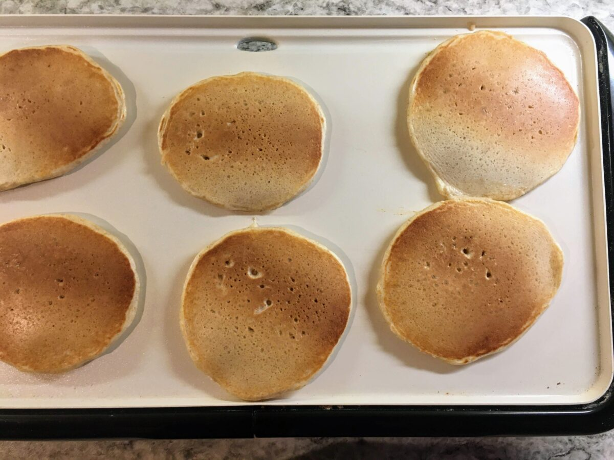 Sourdough pancakes cooking on an electric griddle.