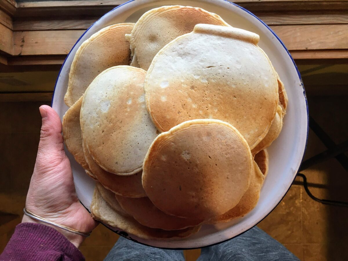 A huge pile of sourdough pancakes on a dinner plate.