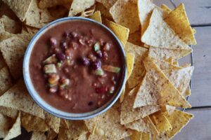 Top view of a bowl of avocado bean dip surrounded by tortilla chips.