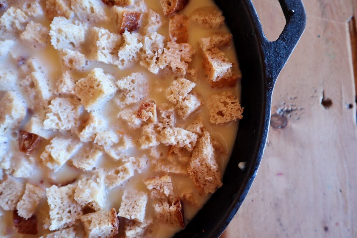 Egg batter and toast cubes in a cast iron skillet to be baked.