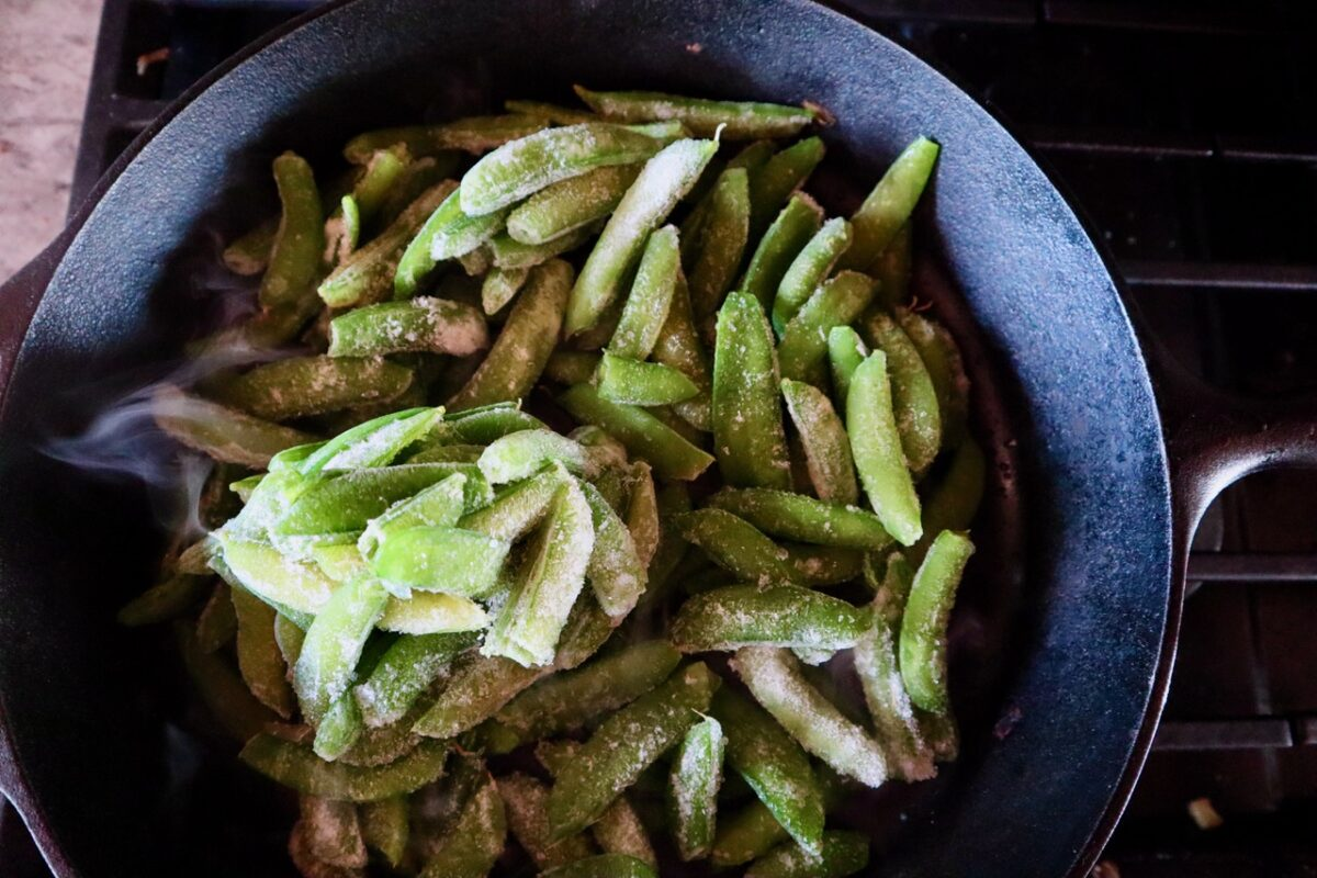 Frozen pea pods in a cast iron skillet to steam.