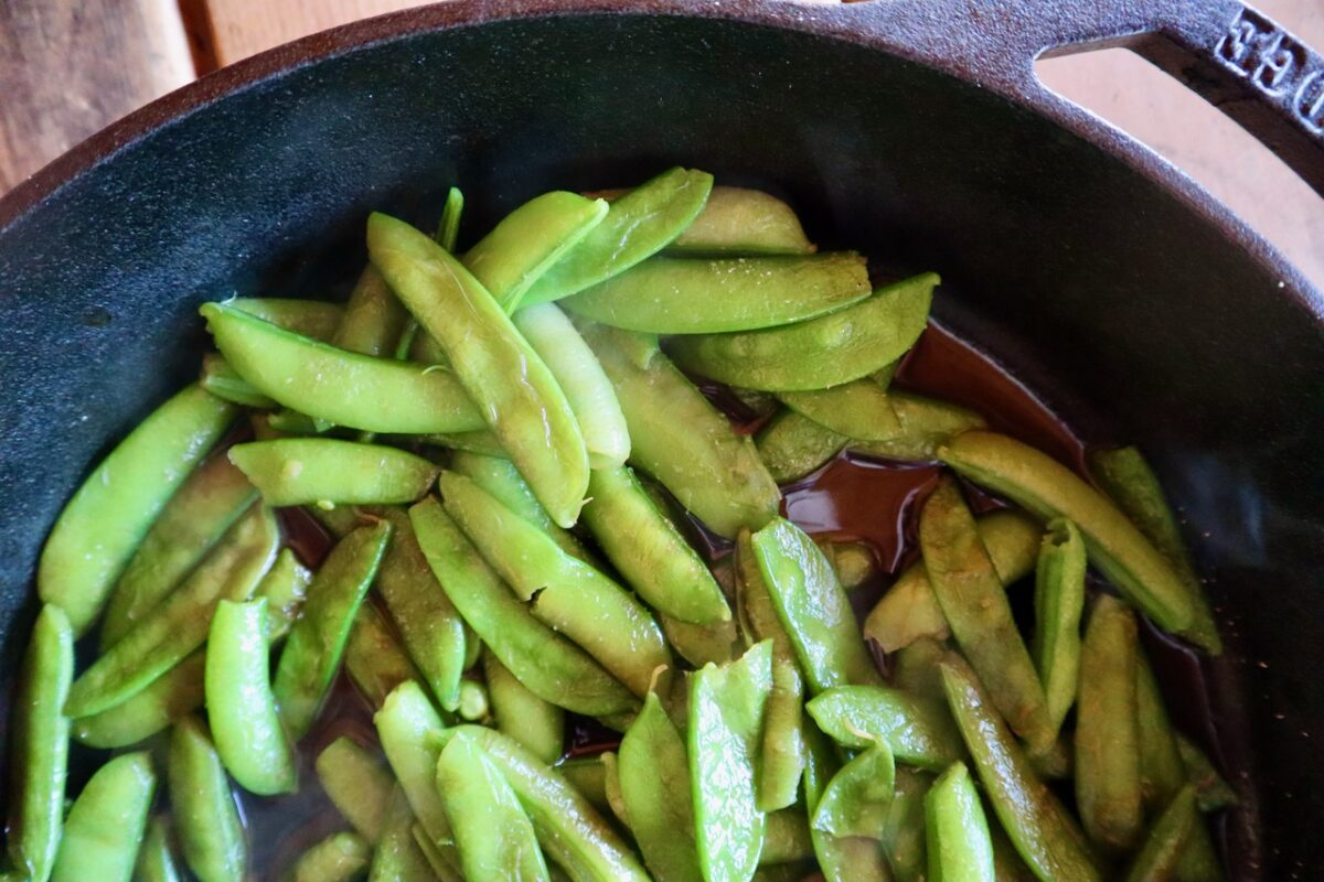 Close up of pea pods cooked in a cast iron skillet.