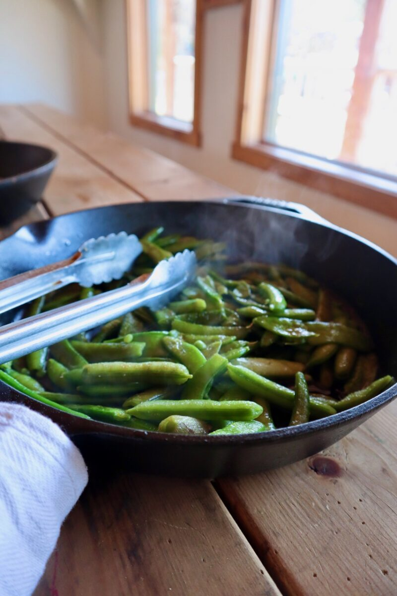 Tongs and steamed pea pods in a cast iron skillet on the table.