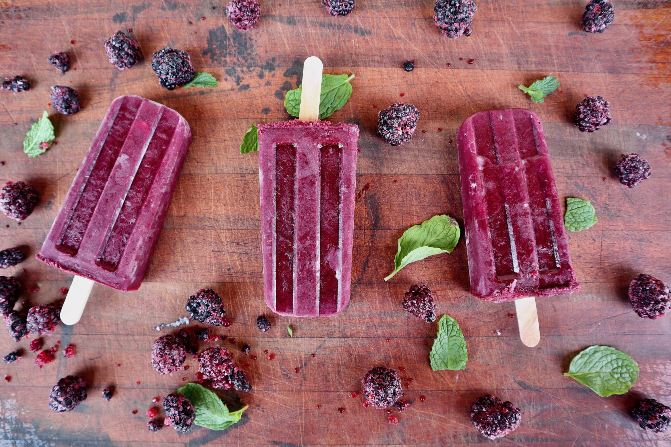 Berry popsicles on a wood board surrounded by blackberries and mint leaves.