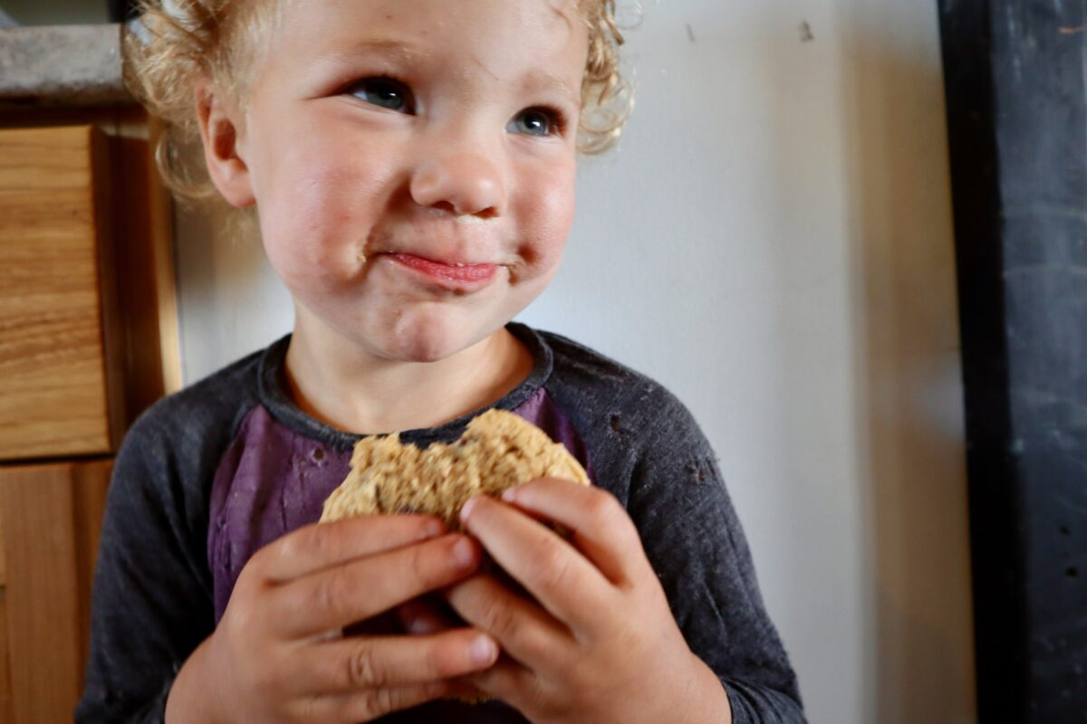 Toddler smiling after a bite of a fresh chocolate chip cookies.