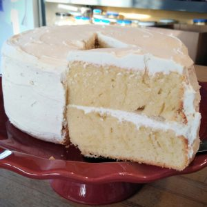 Round layer cake with a gorgeous slice cut out.
